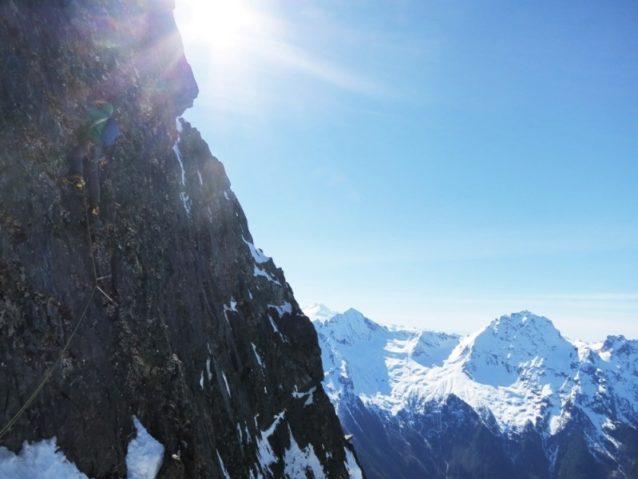ノース・リブの上部を登りはじめるディラン。渓谷の反対側には遠隔のクルシャンを含んだアメリカとカナダの国境にある山々が見える。Photo:Colin Haley
