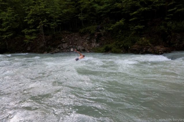 最初の、かつ最も困難な徒渉で氷河から流れ出た川を泳ぐリック。Photo: Weston Boyles