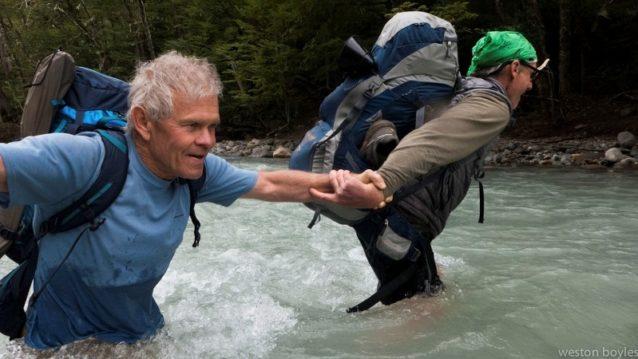 川のフェリー第2弾。今回はパックを担いだまま、老年の男を真ん中にして徒渉。Photo: Weston Boyles
