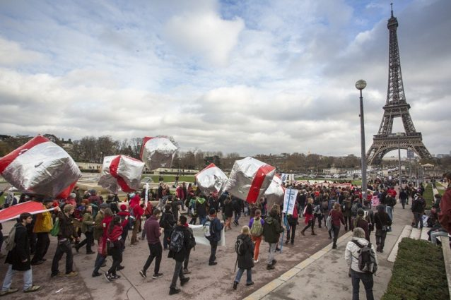 「レッドライン」抗議運動が凱旋門からエッフェル塔に移動。アクティビストらは交渉者に超えてほしくない線を象徴した赤を着用した。Photo: Kodiak Greenwood