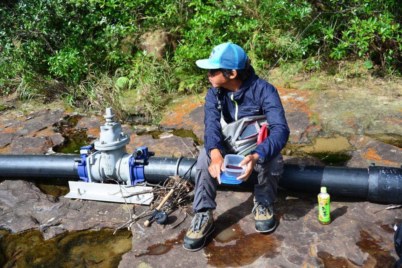 釣りの合間にパイプに腰掛けて昼食。管が岩盤に直接固定されているのがよく分かるだろう。写真:中根淳一