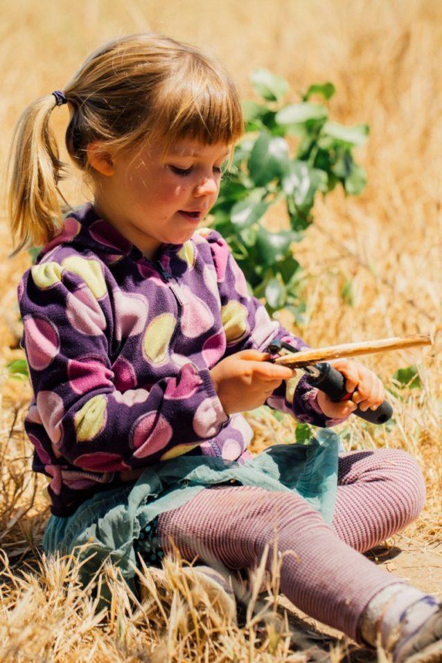 子供たちは木の棒を削るために、各自の技量によって野菜用ピーラーかナイフを選ぶ。彼らは鋭い道具を使う前に落ちた枝や棒を使って「血の輪」を作り、他の子供たちにその輪の外側が安全であるとわかるようにする。Photo: Kyle Sparks