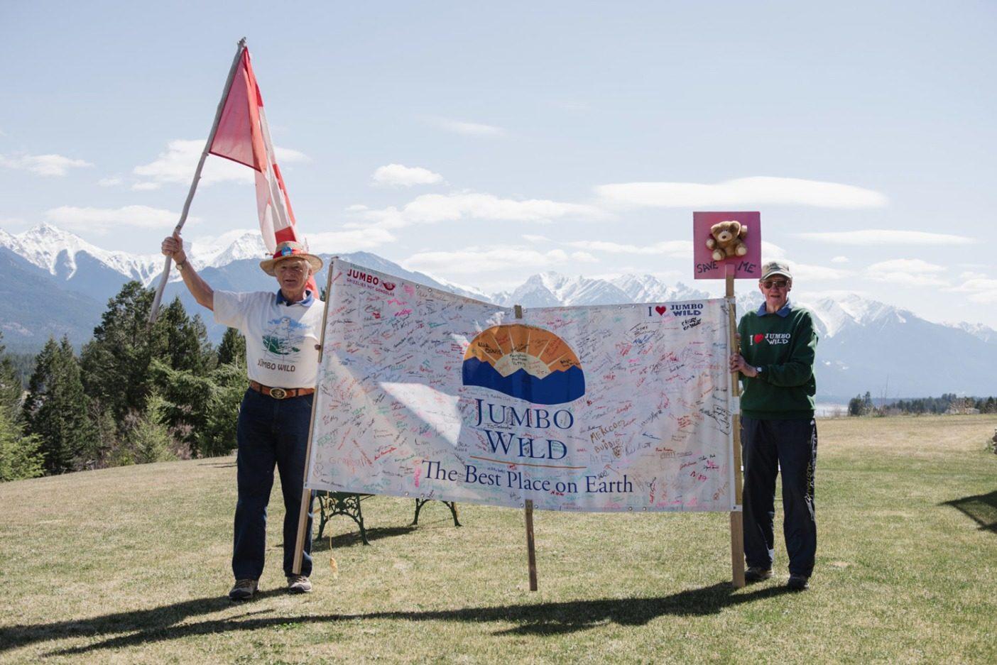 インバーミア・バレーの多くの人びとがジャンボ・グレーシャー・リゾート開発阻止への支持を表明して署名したバナーを掲げるボボ・キャンプソールとジム・ギャロウェイ。Photo: Garrett Grove