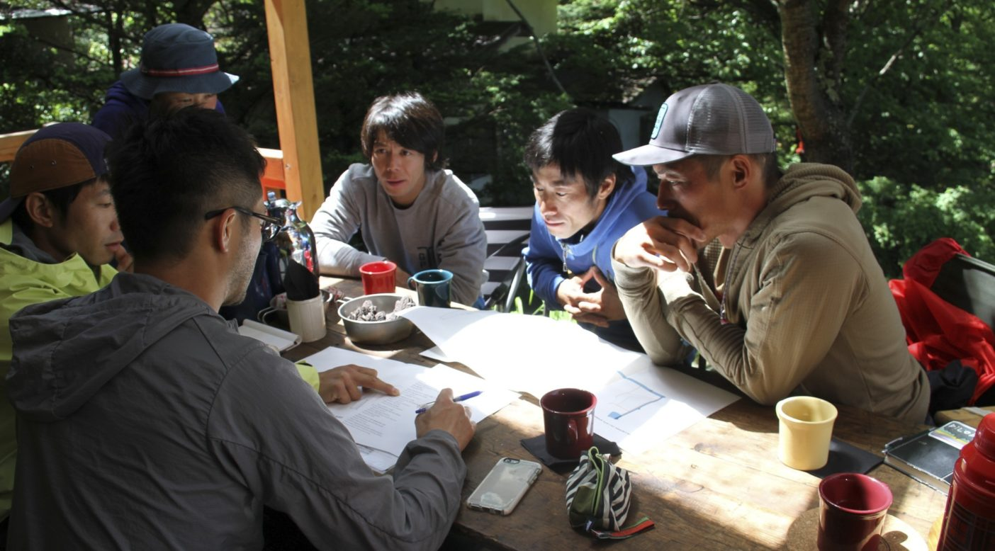 八ヶ岳山麓で、湿気が多くてベタベタする日本の春から秋にかけての雨の日のトレッキングのための雨具について話し合う日本のクライミング・アンバサダーたち。写真:片桐星彦