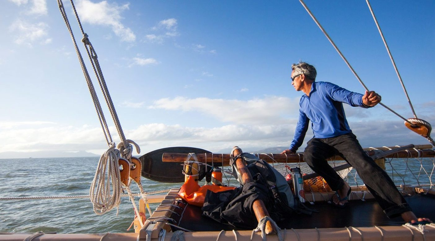 グレート・バリア・リーフを抜ける航路にてマカアラ(覚醒)の状態を保つ、 ポゥ航法師のナイノア・トンプソン。ポリネシア航海協会の代表でもあるナイノア船長 は、人生の半分以上におよぶ35年間にわたってホクレア号の舵を取り、祖先の伝統 に習って星、風、月、波、鳥、魚を頼るべき指標としてきた。Photo: John Bilderback