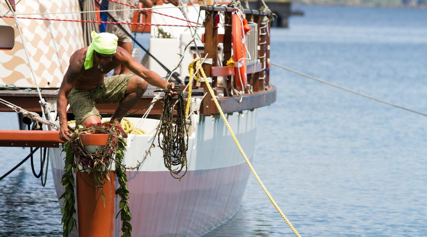 世界航海の開始にあたるヒロでの出航儀式中、レイを船首にかけるヒキアナリア 号の乗組員のエルヴェ・マラエタアタ。パレカイ(「防波堤」または「海から防御する こと」の意)での儀式は、旅立つホクレア号の乗組員を守り慈しむため、地元地域 からの温かさとアロハによって行われた。Photo: John Bilderback