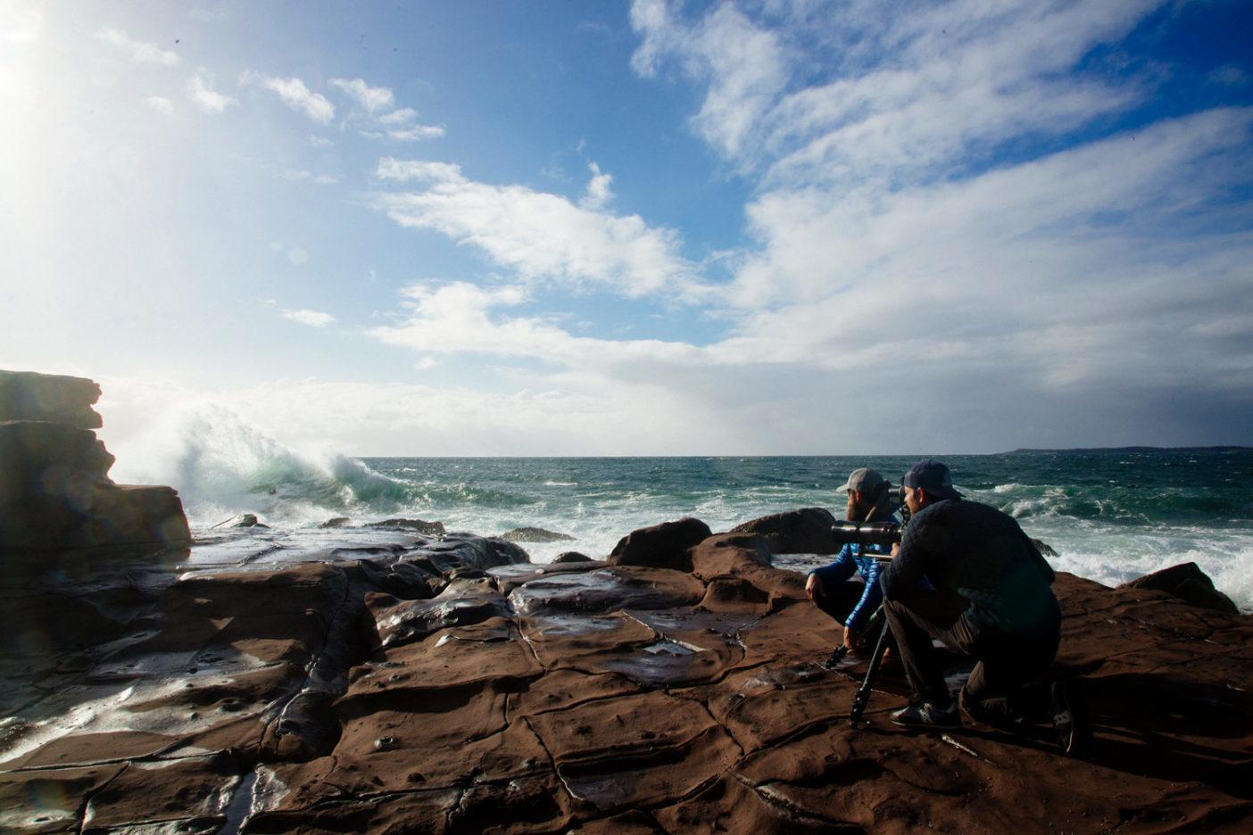 オーストラリアの沿岸で水と岩が合流する危なげな場所をレイがくぐり抜ける様子を捉えるキースとアンドリュー。Photo: Donnie Hedden