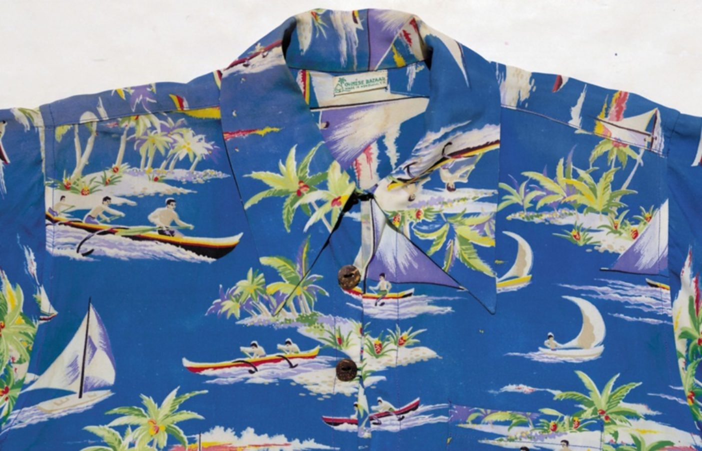 3つボタンのプルオーバーシャツは、よりゆったりとした前開きのアロハシャツの前身。熱帯の島の周りを軽快に走り回るアウトリガー・カヌーがモチーフのこのアロハシャツは、ハワイにインスピレーションを得た初期の柄。カベクレープ、ラベル:Chinese Bazaar, Made in Honolulu, T.H. (Territory of Hawai'i)。 Photo: Patagonia Books