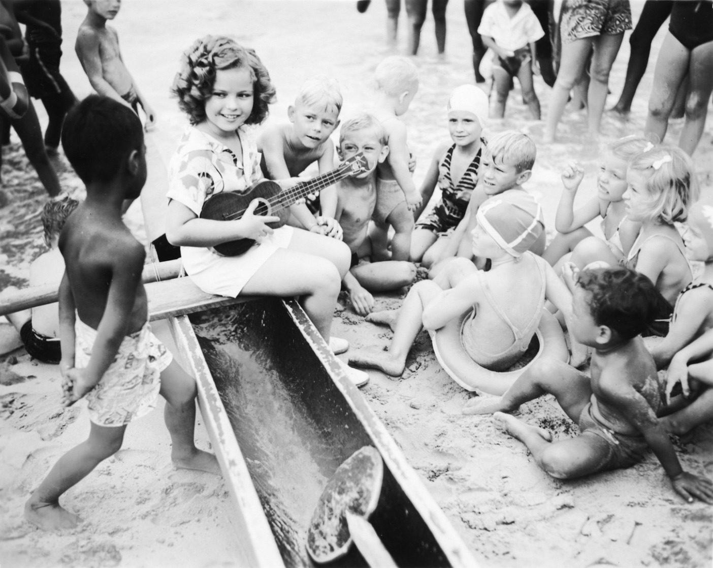 初期のカベクレープ製のアロハシャツを着て、ワイキキビーチで地元の子供たちとウクレレを弾くシャーリー・テンプル。 Photo: courtesy of the Bishop Archives