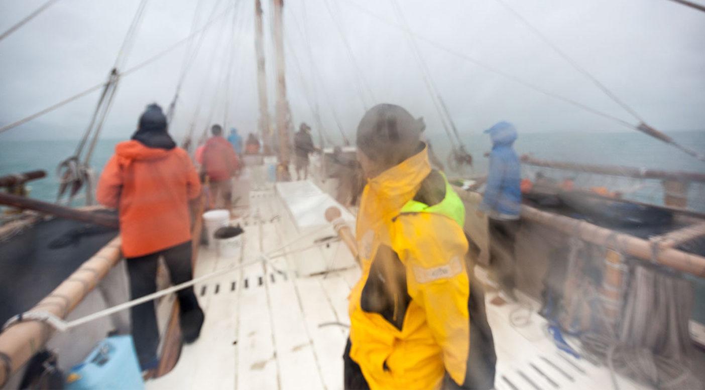 アオテアロアからオーストラリアまでの 12 日間の航路のほとんどで遭遇した 悪天候と、7.5 メートルの波に耐える乗組員たち。ホクレア号のシドニー港到着により、 このカヌーがはじめて太平洋の外へ出たことが記録された。Photo: John Bilderback