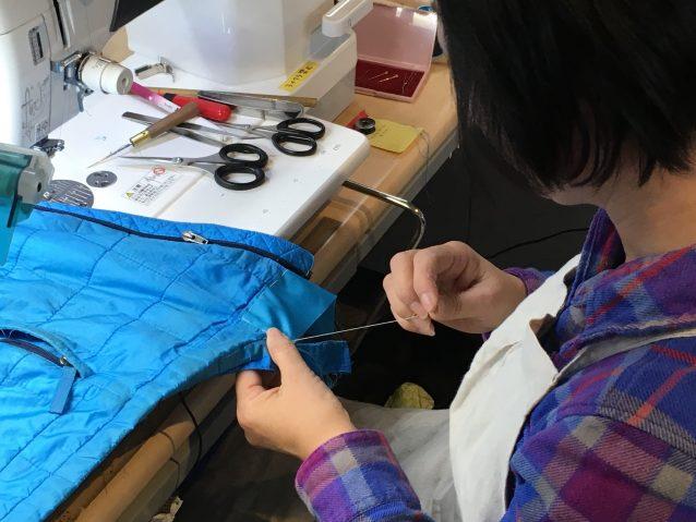 ハイロフト製品の裾の破れ修理。ミシンで縫う前に当て布をしつけする。  写真:パタゴニア日本支社