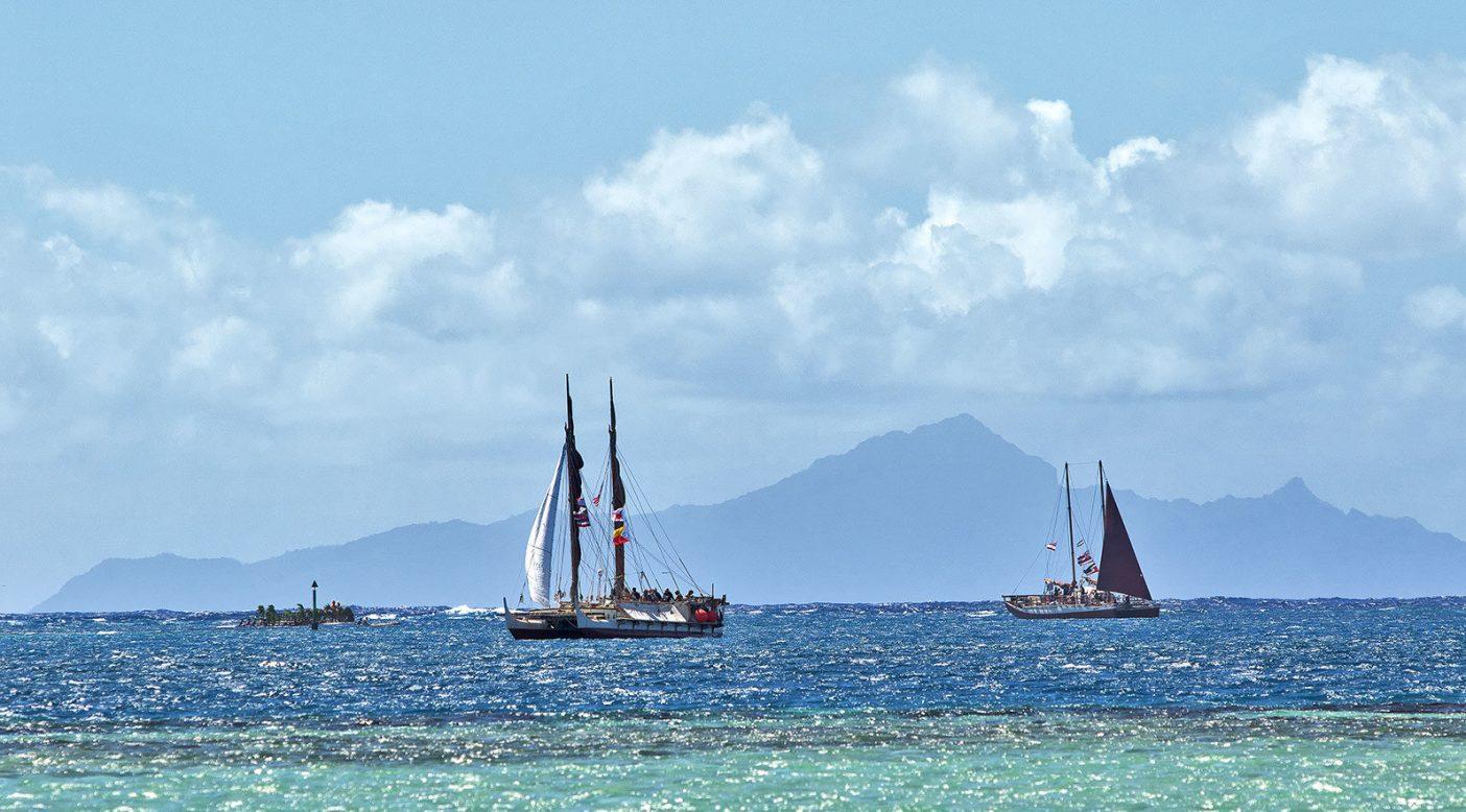 30ノット弱の風に最小限の帆を揚げ、タプタプアテアへの聖なる航路「テ・アバ・モア」に向かうホクレア号とヒキアナリア号。 Photo: John Bilderback