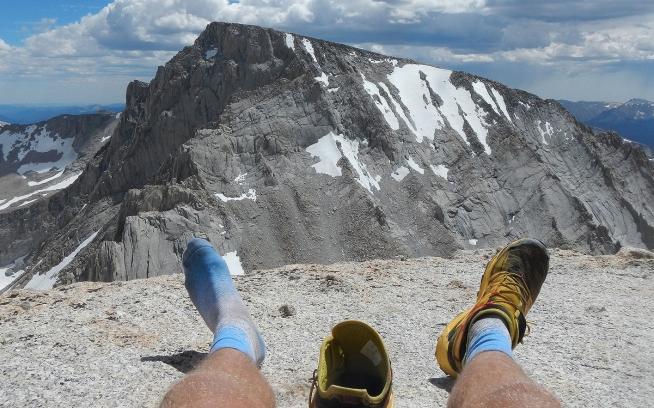 ラッセル山頂でホイットニー山を眺めながらシューズに入った石を取り除く。 Photo: Erik Schulte