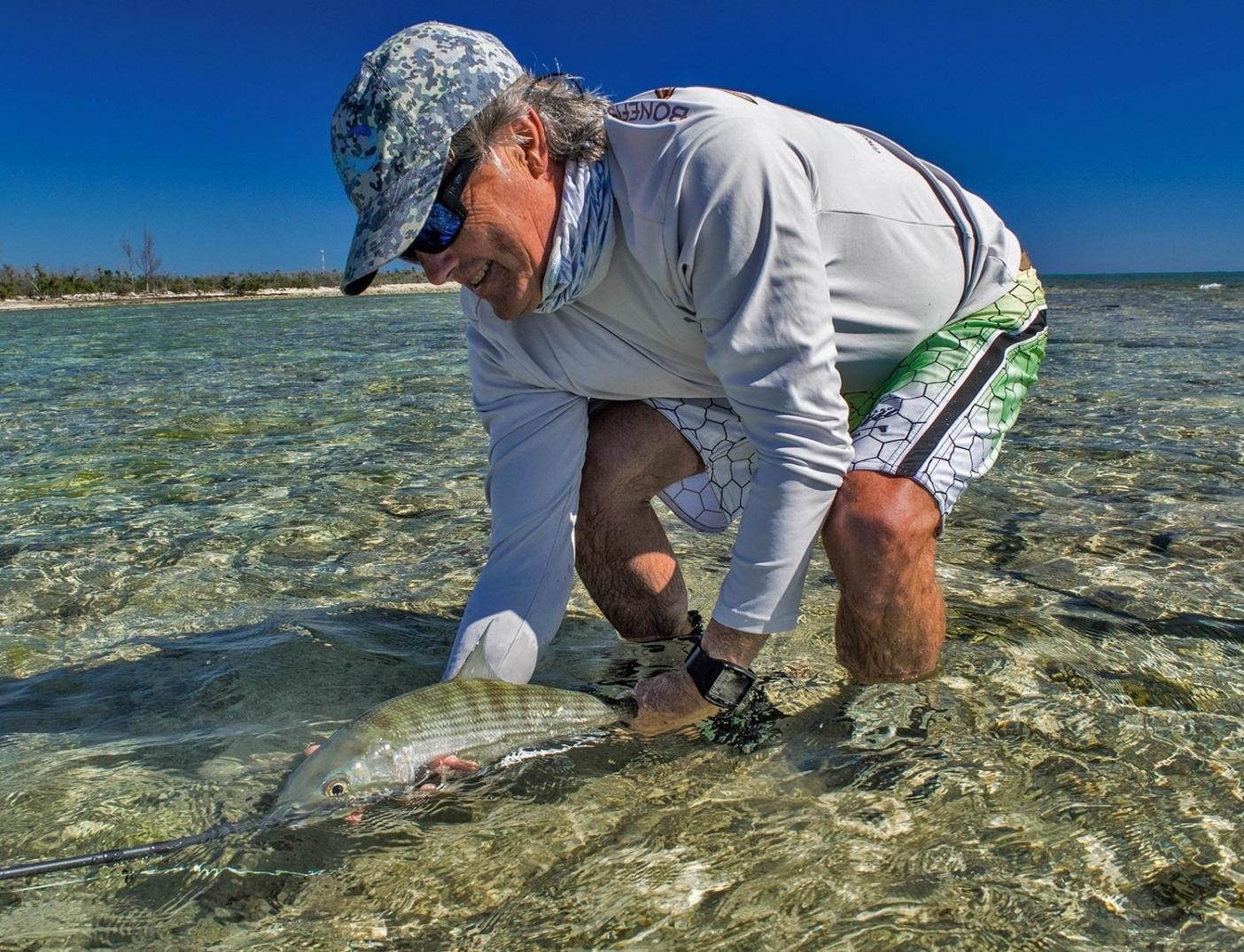 浅瀬のグレーゴーストでボーンフィッシュをリリースするアーロン・アダムズ博士。グランド バハマ島。Photo: Justin Lewis