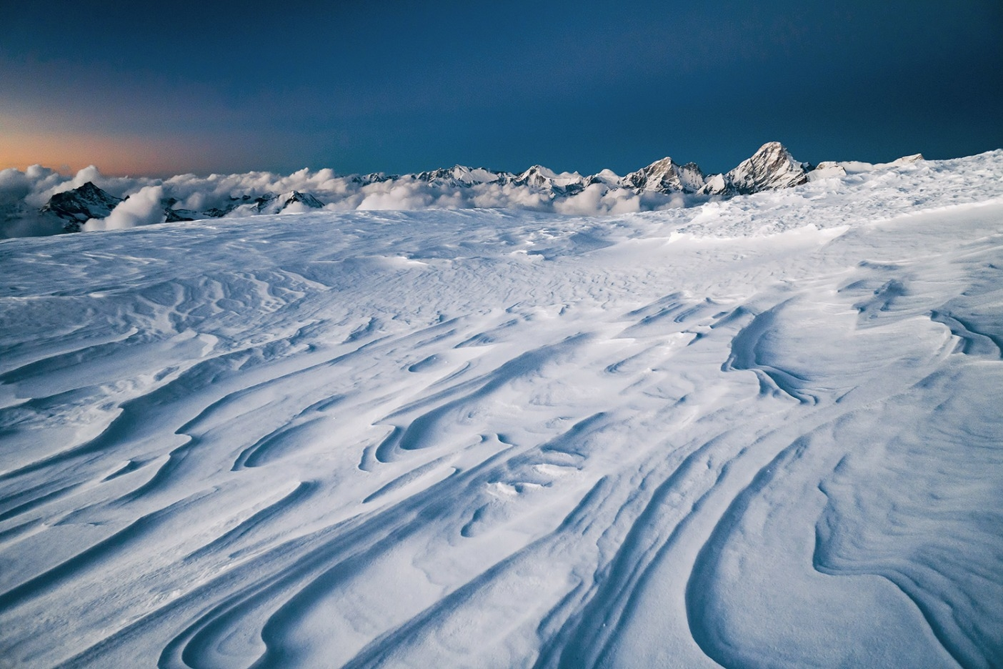 山頂までわずか数百メートルのところに、やっと平らなビバーク地を発見したときは予定よりも遅く、私たちは疲れ果てていた。そこは北側でとても寒く、強い風が雪の上に荒々しい線を刻み出していた。それほどの高所で寝た経験は私たちの誰にもなく、睡眠はほとんど取れなかったが、少なくとも平らだったおかげで静穏な夜空の下で体を休めることはできた。Photo: JASON THOMPSON