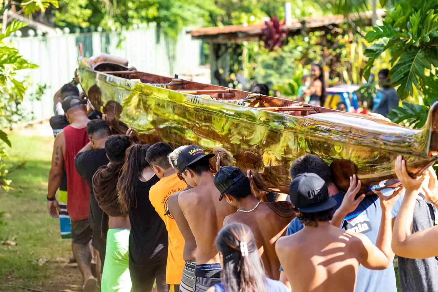 仕事が終わってすっかりピカピカになったウイを肩に担いで、オアフのアウトリガー選手権へと連れていく〈マヌ・オ・ケ・カイ・カヌークラブ〉のメンバーたち。ハワイ州ハレイワ Photo: John Bilderback
