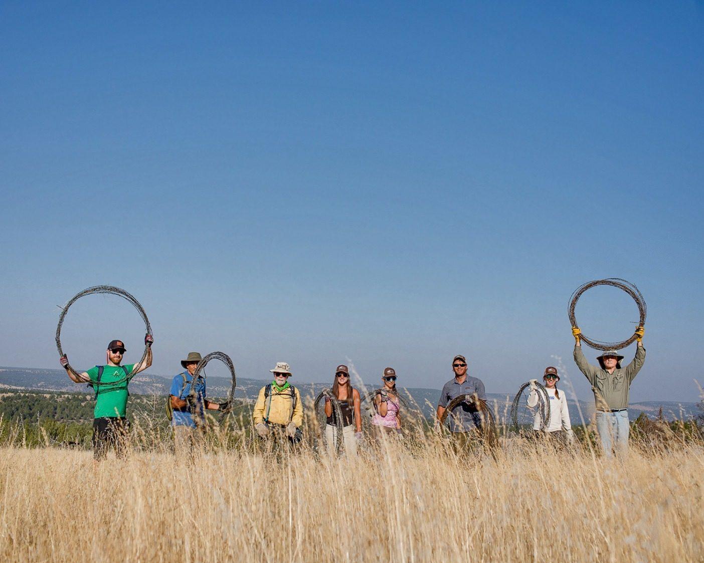 重さ125トンにも及ぶ100キロメートル以上のフェンスをスティーンズ山脈から除去した〈ONDA〉のボランティアたち。最後の有刺鉄線を取り除き、97,000エーカーの野生地をフェンスのない場所にしたことを祝うスタッフ(左から右):アーロン・ヘリクソン、アンドリュー・スーレック、クレイグ・テリー、エリッサ・リンデンメイヤー、アンバー・ラメット、マイケル・オケイシー、コリーン・ハンデルマン、クリフォード・ローン。Photo: Sage Brown