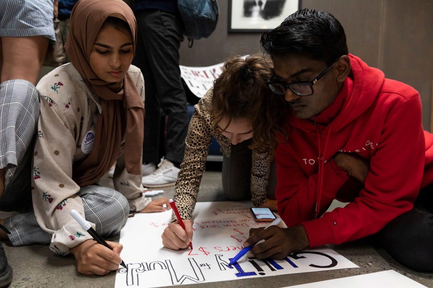 ストライキ前日、ニューヨーク気候ストライキ主催者のアイシャ・シディカとイザベラ・ファラヒ、さらにロサンゼルス出身の気候正義活動家であるケビン・パテルが、アート・プラカードを仕上げる。こうした若い主催者はそのアクティビズムはフルタイムの仕事のようなものだと言う。Photo: Keri Oberly