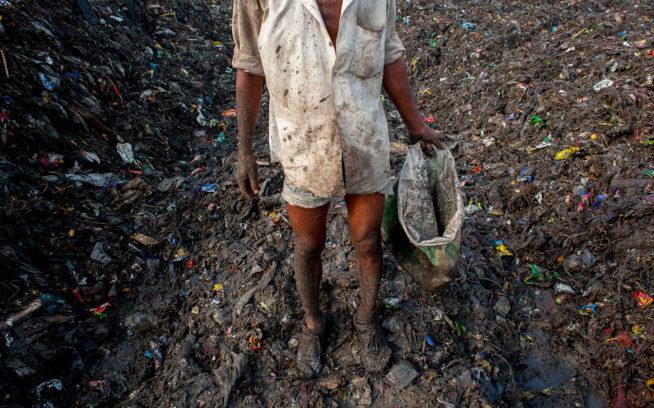 バングラデシュの埋立地でゴミを選り分けながら、しばしの休憩に立ち止まる労働者。ゴミ捨て場での連続勤務時間は1日平均10時間。Photo: BORJA SANCHEZ-TRILLO/GETTY IMAGES