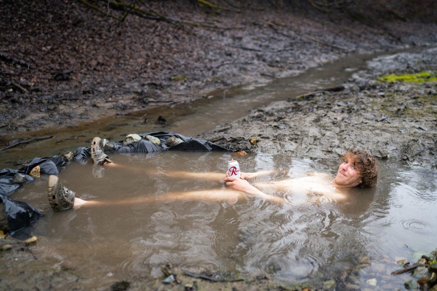 高山での厳しいミッションの後は、少しのビタミンR(レーニアビール)と、手作りの泥だらけな温かい水たまりでの入浴を越えるものはない。スティキーンでのリラックスタイムで裸になるエリック・ジョンソン。Photo: Jasper Gibson