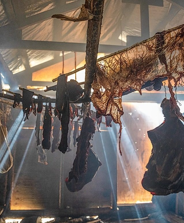 カリブーの肉は燻し小屋に吊るされ、それから冬のために冷凍庫に保存される。若者は長老たちから、冬を過ごすための食料の準備と保存の方法を学ぶ。 Photo: Keri Oberly