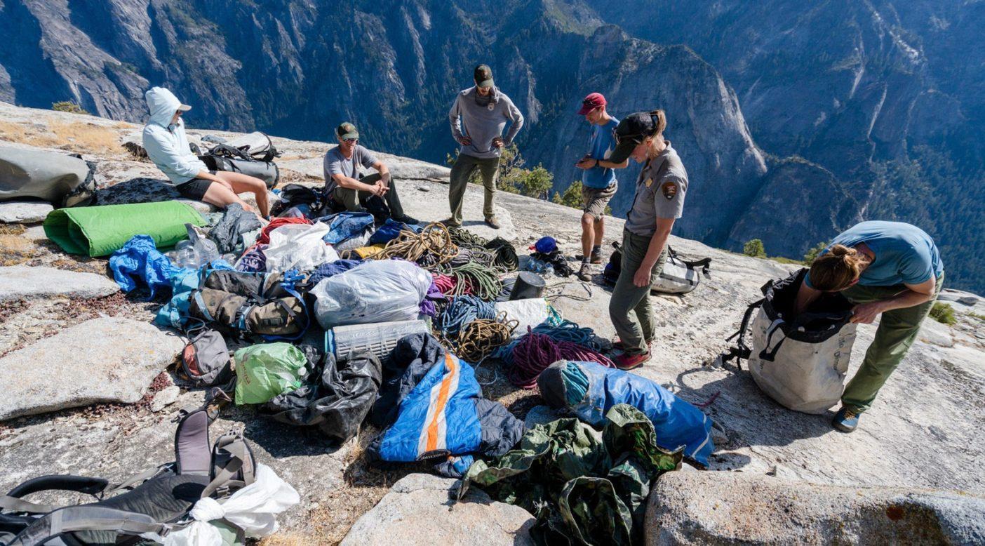 クライミング・レンジャーやクライミング管理人、ボランティアからなるボランティアチームが、エル・キャピタンの頂上にある多くの隠し場所の1つから回収した巨大なゴミの山を見つめる。Photo: Eric Bissell