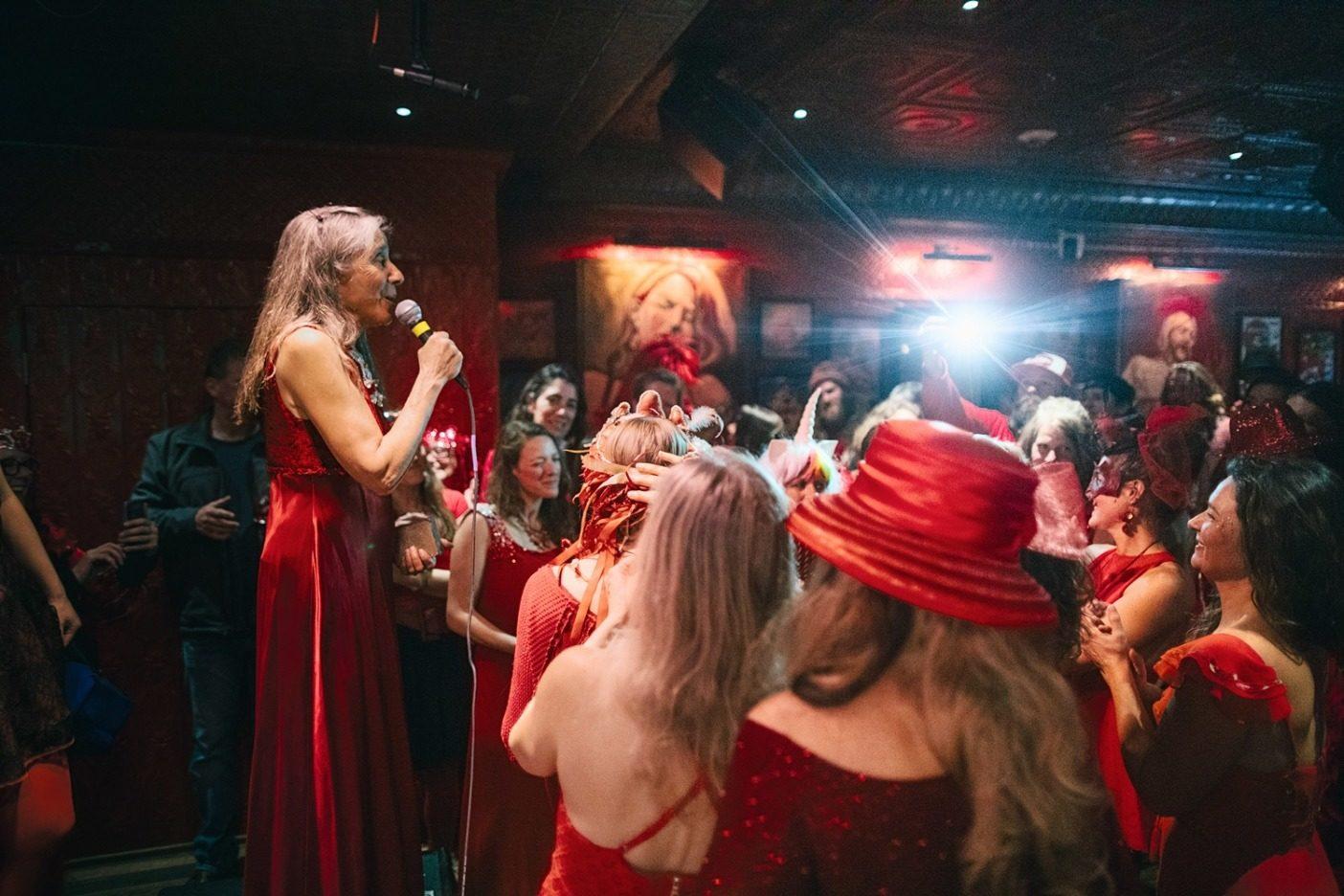 第 11 代「レッド・レディ」のスー・ネイビーは、レッド・レディの鉱山反対 運動に 1977 年以来積極的に関わってきた。2019 年 3 月上旬に開催された 「レッド・レディを救う舞踏会」でのこの写真に写るのは、結果を心待ちにする群衆の前で、第 42 代「レッド・レディ」の受称者を発表する彼女の姿。Photo: Forest Woodward