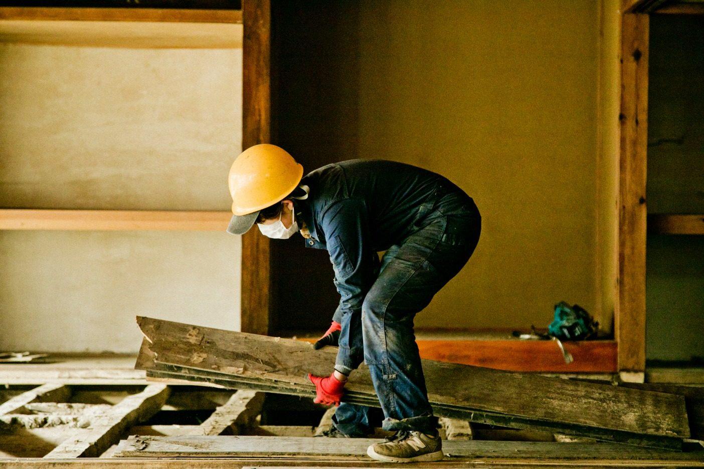 割れないように、一枚一枚丁寧に。床板のさね(凸凹の加工)を確認しながら、リビセンのスタッフ、松澤美也さんが古い床板をはがしていく。写真:五十嵐 一晴