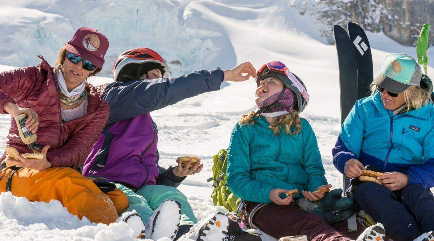 肉、チーズ、1週間前のベーグル、そして石で挽いたマスタード。山でのグルメなランチ休憩で充電するナン・クレストとその娘のセーラー・カベアリー、そしてローン・ハービーとシェリル・アルブレヒト・ハービー。ペイトー・ハットの上への休日旅行で、午前中に繰り返しパウダースノーの緩い傾斜を滑った後だ。Photo:Kennan Harvey