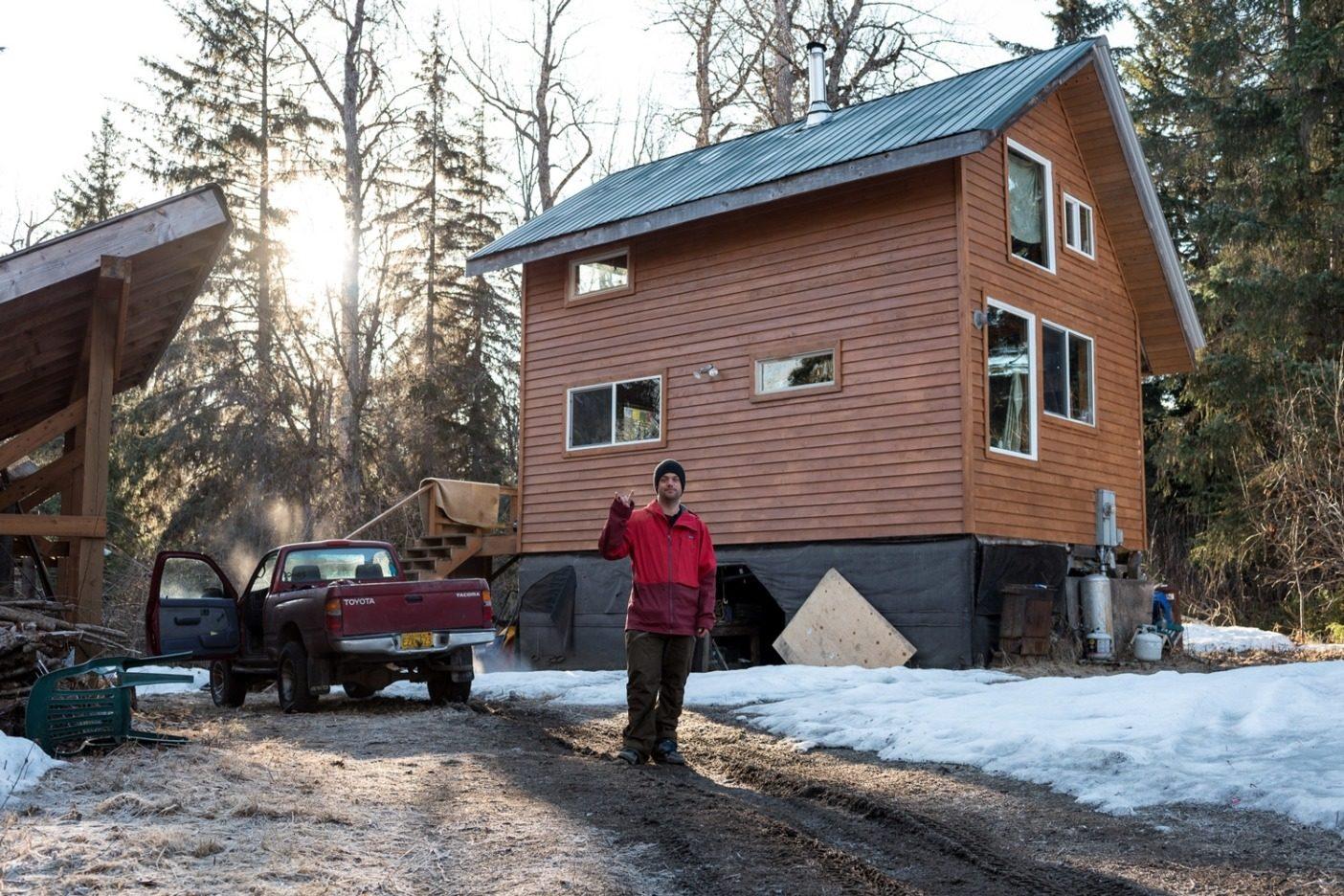 アラスカ州ヘインズの郊外42キロメートルの場所にある自宅の前に立つベル。シンプルな2階建ての家には、屋外コンポストトイレ、暖房用のウッドストーブ、調理用のプロパンコンロ、キッチンに設置するオンデマンド式のシャワーがある。Photo:Colin Wiseman