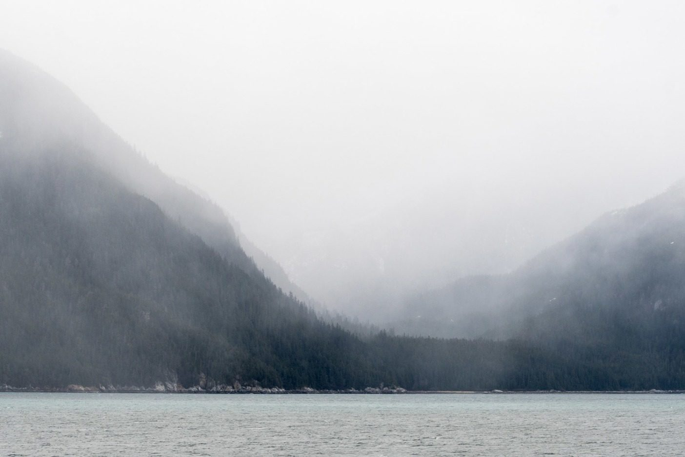 アラスカ州、ジュノーとヘインズの間でアラスカ・マリン・ハイウェイ・フェリーから望む霧に包まれたリン運河の山々。提案されている予算削減は、数多くの沿岸コミュニティと、彼らが頼る観光業の生命線であるアラスカのフェリー制度民営化に繋がる可能性がある。写真:Colin Wiseman