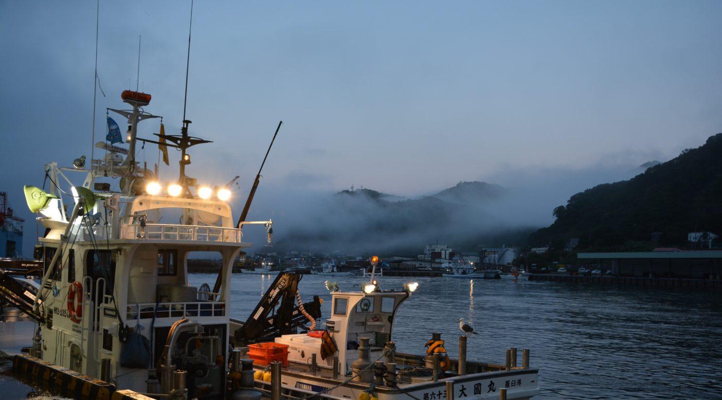 知床連山の尾根に霧が立ち込める早朝、静かに一仕事を終え帰港した漁船が佇む羅臼港。写真:村上春二