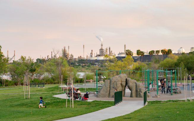 カリフォルニア州ロサンゼルス、ウィルミントン地区の公園の背後にある石油精製所。NAACP(全米黒人地位向上協会/全国有色人種向上協会)の調査によると、全米の91郡の670万人以上のアフリカ系アメリカ人と低所得者が居住する地域の近くでは、石油精製所が建設中であるか、すでに存在している。Photo:Michael Estrada