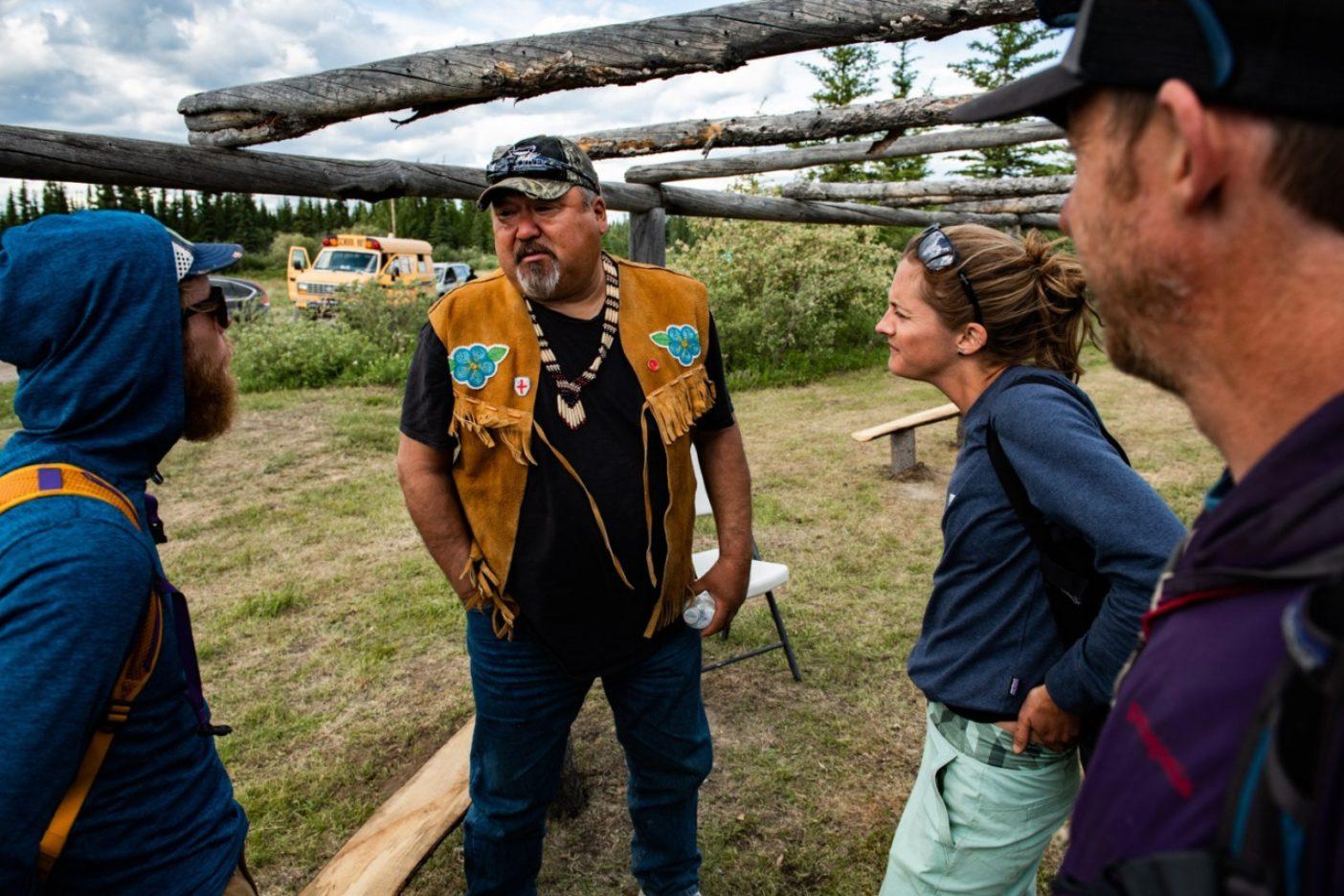 2019年の「北極圏先住民気候サミット」で、グウィッチャー・ズィー(現在のフォート・ユーコン)の第2首長マイク・ピーターから温暖化における狩猟の問題について学ぶルーク・ネルソン、クレア・ギャラガー、トミー・コールドウェル。Photo:Austin Siadak