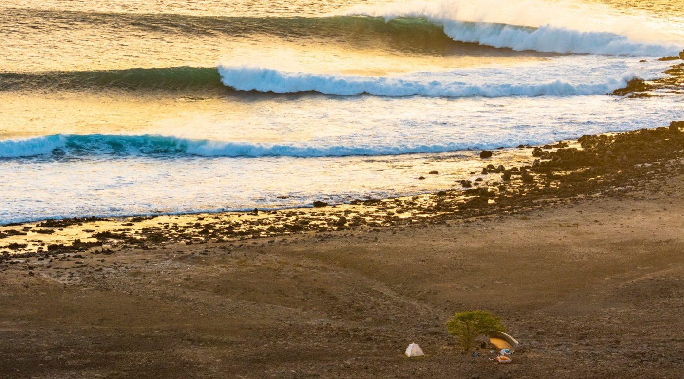 太陽に灼かれ、強風に打たれる、岩だらけの過酷な場所。大西洋に浮かぶ秘密の島にテントとタープで作ったこの海沿いのキャンプが、グレッグ・ロングとピート・ギアルとアル・マッキノンの仮住まいとなった。photo : Al Mackinnon