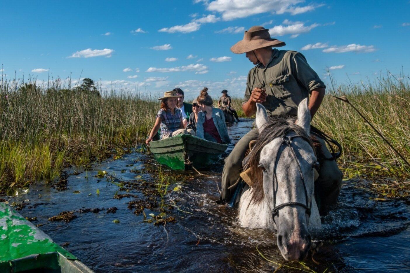 イベラのエステロス(湿地帯)を伝統的なカヌーで旅するのを楽しむ旅行者たちを振りかえるフェデリコ。野生動物のイベラへの復帰により、この地方への観光客数はますます高まり、フェデリコのような地元ガイドの職も増えている。