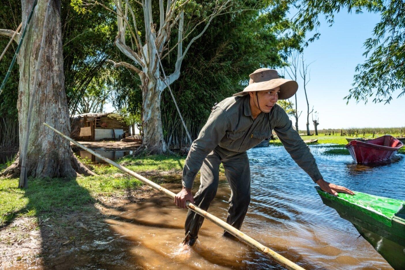 公園の端にある小さな農場からイベラの湿地帯へとカヌーを押し出すフェデリコ・フェルナンデス。子供時代、彼はイベラの中心にあるカランボラと呼ばれる小さなコミュニティ(パラヘ)に住んでいた。そこで家族は牛、豚、鶏と、乾燥した土地の小区画で野菜を育てた。彼が10歳のとき、彼の家族は職を求め、彼が学校へ行けるようにコンセプシオンの街へと越した。彼は故郷に戻れたことを喜んでいる。