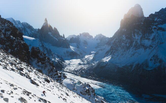 トーレとフィッツロイ(チャルテン)の山塊に太陽が沈む頃、後退するトーレ氷河にそびえる南の尖峰をバックに弧を描く地元ガイドのマーリン。アルゼンチン、ロス・グラシアレス国立公園 写真:マシュー・タフツ