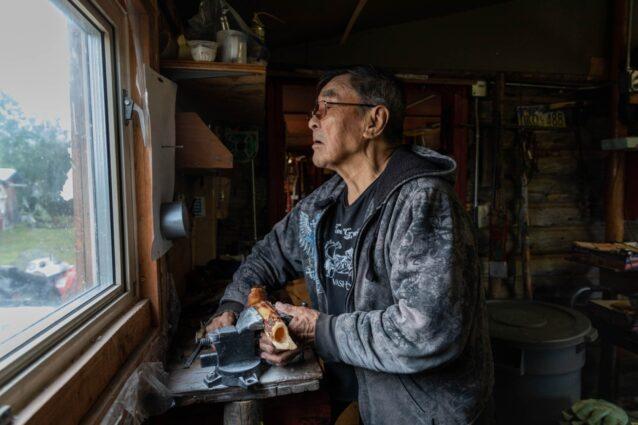 ヴァシュラジ・クーの自宅で装飾品を作るため、ムースの骨の切断準備をする長老ギデオン・ジェームス。グウィッチンは動物すべてを利用し、何も無駄にしない。カリブーと聖なる土地の保護を声高に提唱するギデオンは、「神聖さを守るとき、我々は動物を守る」と言う。Photo:Keri Oberly