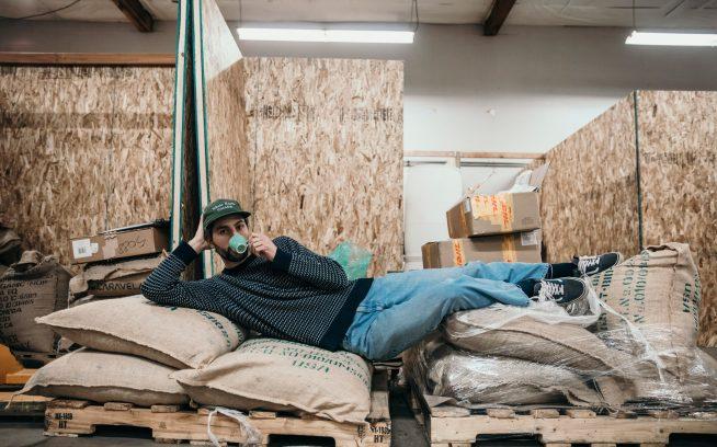 リジェネラティブな農業慣行と環境スチュワードシップにひらめきを得た彼の新企業オーバービューコーヒーのポートランドの焙煎所でくつろぐパタゴニアのスノーボード・アンバサダー、アレックス・ヨーダー。Photo: Johnie Gall